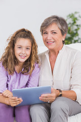 Child and her grandmother looking at the camera with tablet pc
