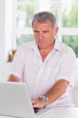 Old man using laptop seriously