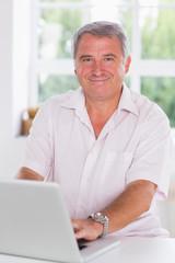 Old man using laptop smiling