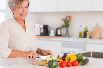 Elderly woman cutting vegetables on a cutting board with a smile