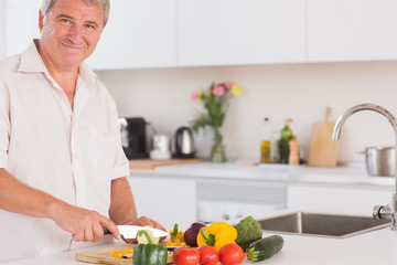 Old man smiling and preparing vegetables