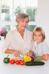 Granny cutting vegetables with her grandson