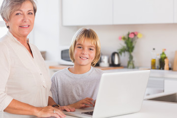 Grandmother and child looking at the camera with a laptop