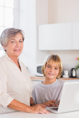 Child and grandmother looking camera with a laptop