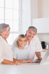 Grandparents and child looking at camera with a laptop