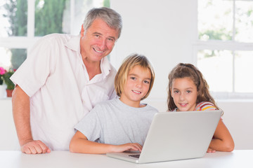Grandfather and children looking at the camera with laptop in fr