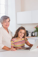 Smiling grandmother and child looking at the camera with laptop