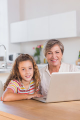 Smiling child and granny looking at the camera with laptop
