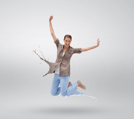 Woman jumping with clothes turning to paint splatters