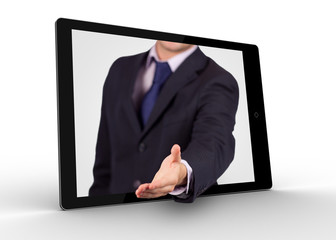 Businessman reaching out from tablet for handshake