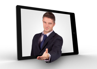 Businessman reaching out from tablet for a handshake