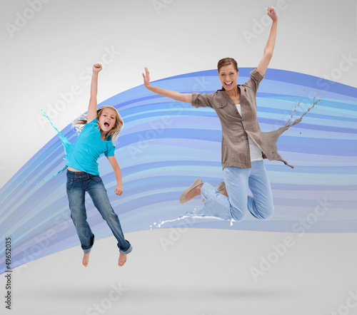 Woman and daughter jumping with clothes turning to paint splatte