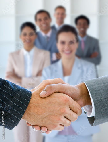 Businessmen shaking hands with team behind them