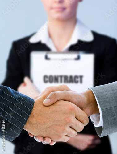 Businessmen shaking hands with contract behind them