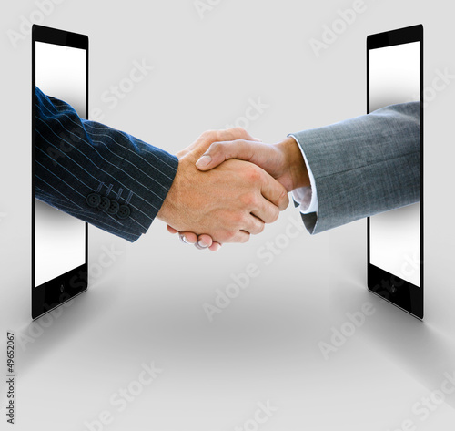 Businessmen shaking hands from digital tablets