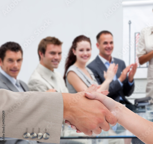 Businessman and woman shaking hands in presentation