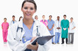 Woman doctor standing in front of her team in row