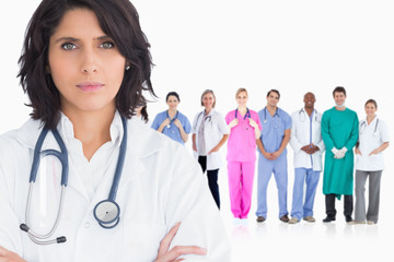 Woman doctor standing arms crossed in front of her team