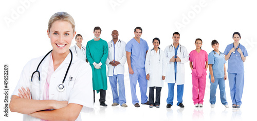Smiling doctor standing in front of her medical team in line