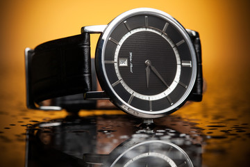 luxury watches with a leather strap on the orange background