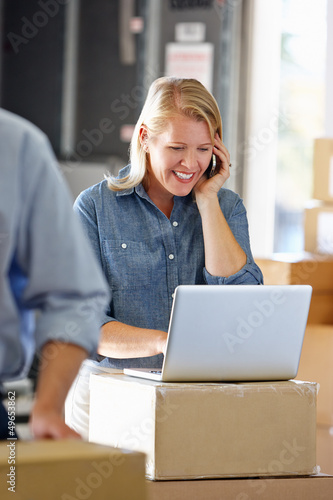 Female Manager Using Mobile Phone In Distribution Warehouse