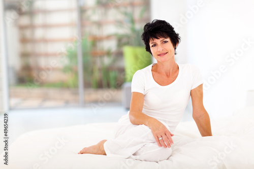beautiful middle aged woman sitting on bed