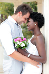 Multiracial wedding couple posing outdoors