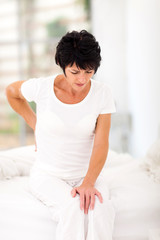 middle aged woman sitting on bed having back pain