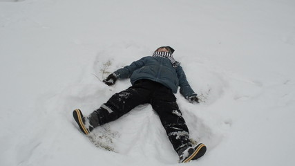 little boy rejoiced winter day and make an snow angel