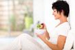 elegant middle aged woman sitting on bed and eating salad