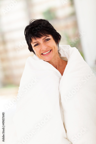 cute middle aged woman covered by duvet at home