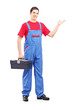 Full length portrait of a repairman holding a tool box and gestu