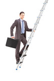 Full length portrait of a businessman climbing a ladder
