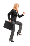 Full length portrait of a businesswoman with a briefcase making