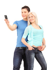 Attractive young couple taking a photo with a mobile phone