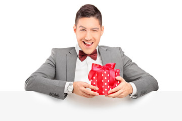 Charming young man holding a present and posing behind panel