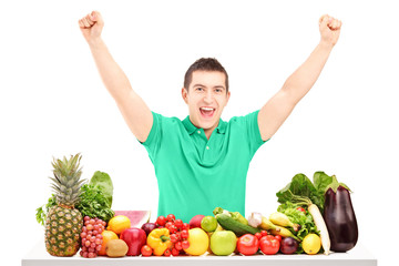 Excited man raising hands and posing with a pile of fruit and ve