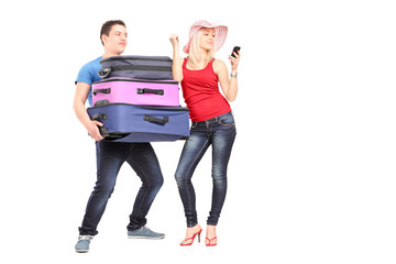 Frustrated man carrying his girlfriend's baggage while she is ma