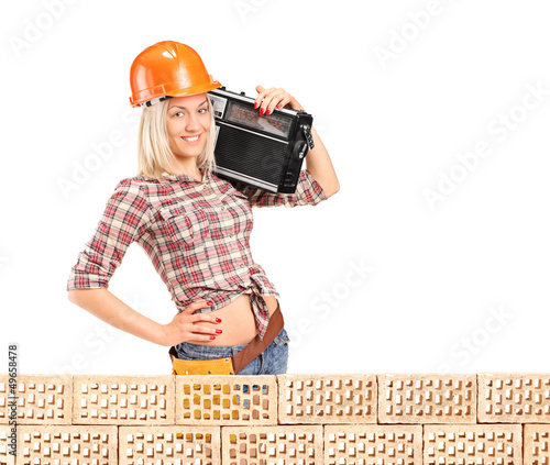 Female construction worker with radio posing next to a pile od b