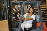 Woman Driving Fork Lift Truck In Warehouse