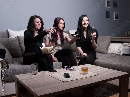 three women watch television and eat popcorn