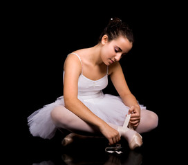 Ballerina putting her ballet shoe against black background.