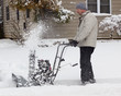 Man using snow-blower after winter storm