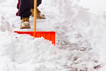 Close-up as man shovels snow