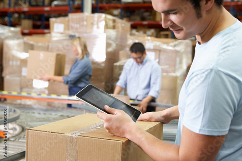 Poster Industrial geb. Worker Using Tablet Computer In Distribution Warehouse
