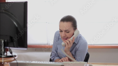 Young woman overhearing a phone conversation in the office