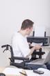 junger Rollstuhlfahrer am Arbeitsplatz