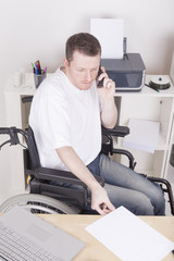 young man in wheelchair at work, having a phone call