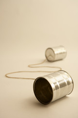 Two tin cans connected with string, close up