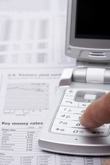 Finger touching mobile phone on a financial paper